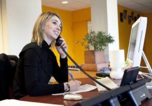 standardiste avec un beau sourire répondant au téléphone